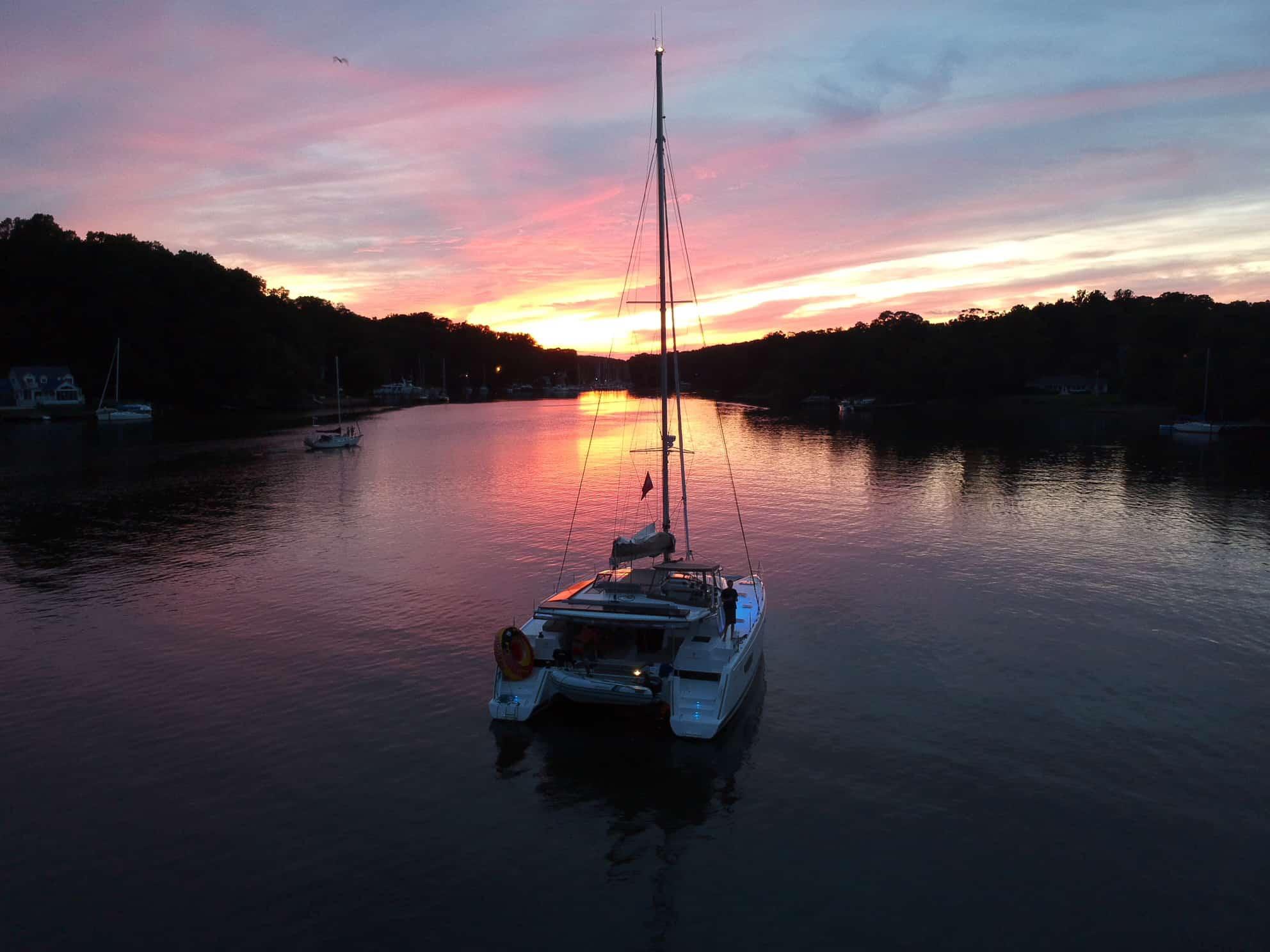 A sailing catamaran at sunset