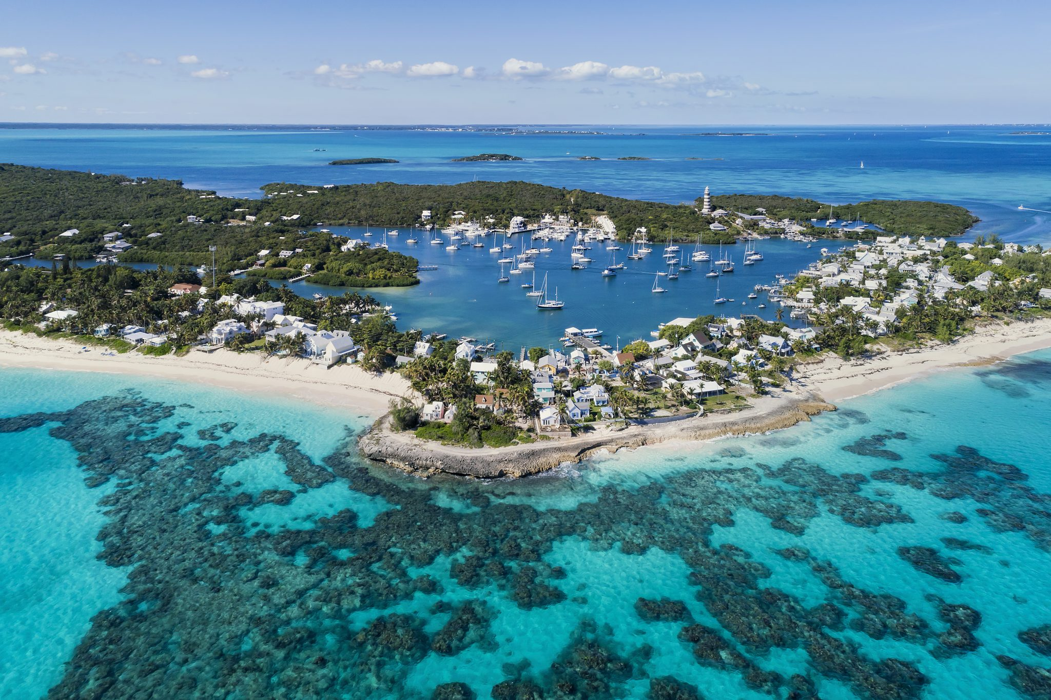 Aerial view of the harbour, beach and lighthouse in Hope Town on Elbow Cay off the island of Abaco, Bahamas.