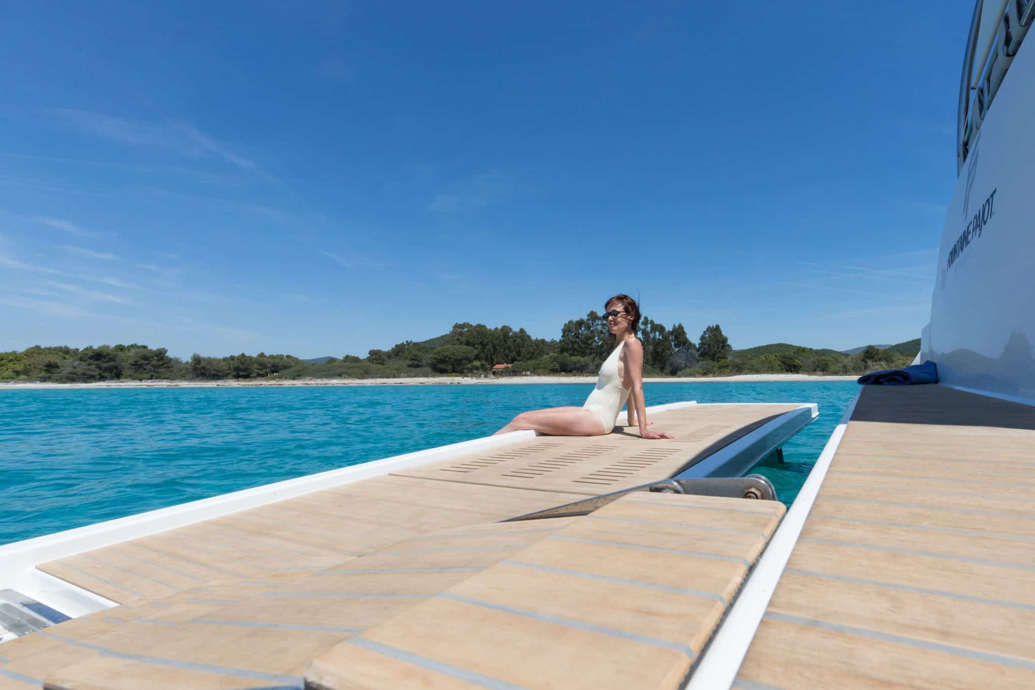 A woman relaxing on the bow of a yacht