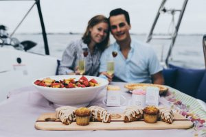 A man and woman enjoying lunch on a yacht