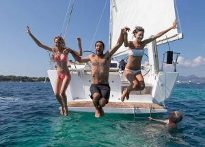 A group of friends jumping into the water from the stern of a yacht