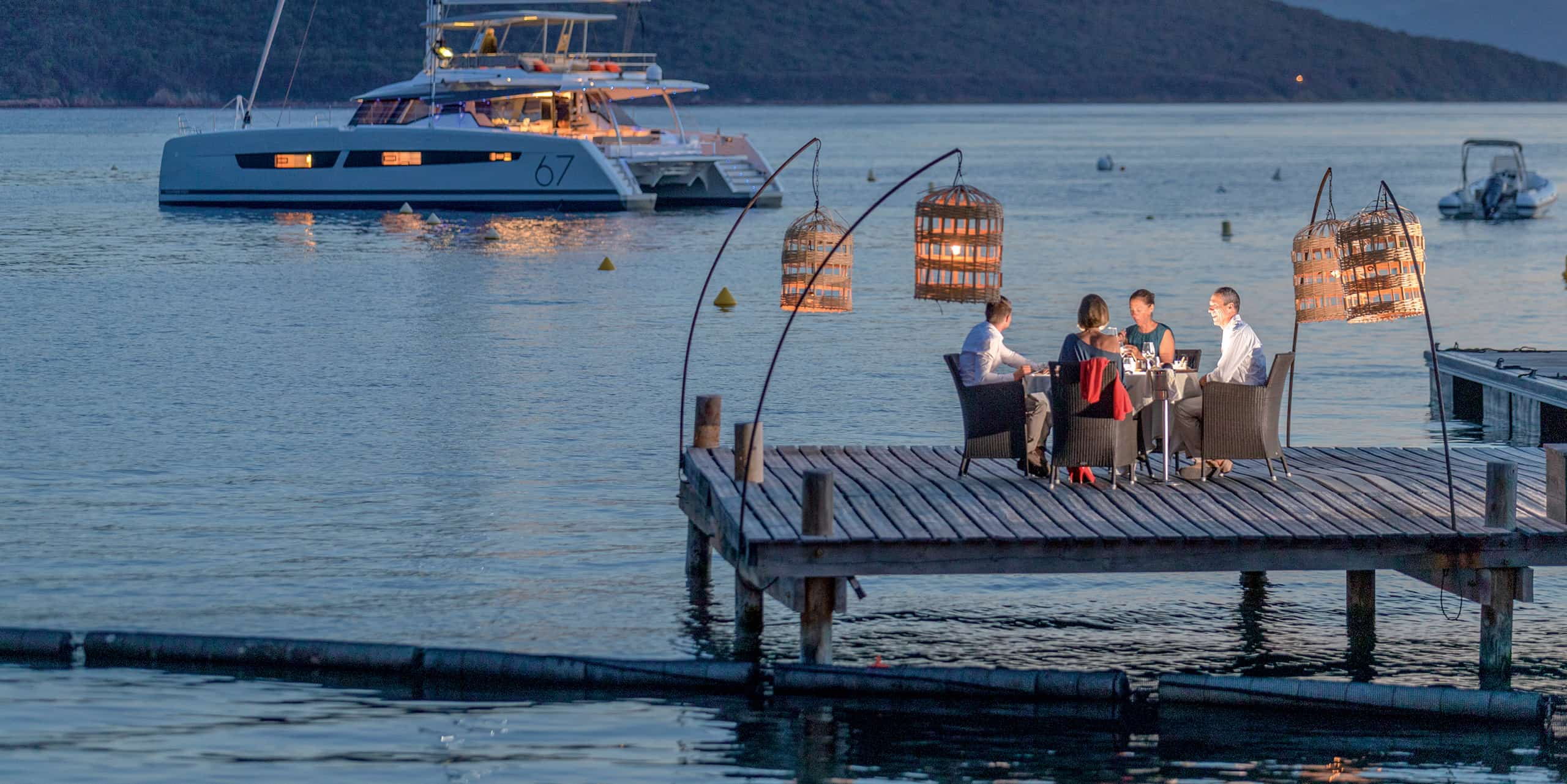 A group of friends eating on a dock with their boat anchored in the distance