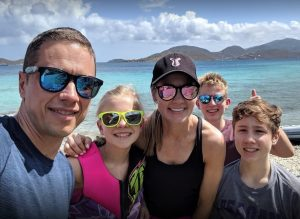 A family posing for a picture with the British Virgin Islands in the background