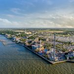 An aerial view of the Kemah shoreline with boats docked and an amusement park on the pier
