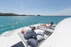 A man and woman lounging on the deck of a catamaran