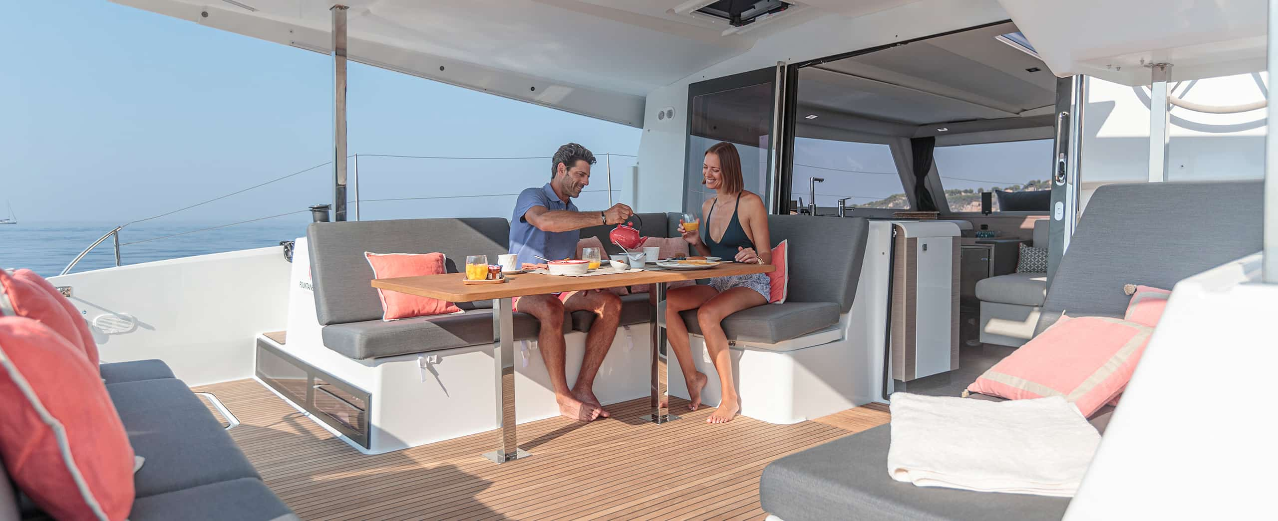 A man and woman having lunch on the deck of a yacht