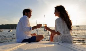 A man and woman drinking wine on the bow of a yacht