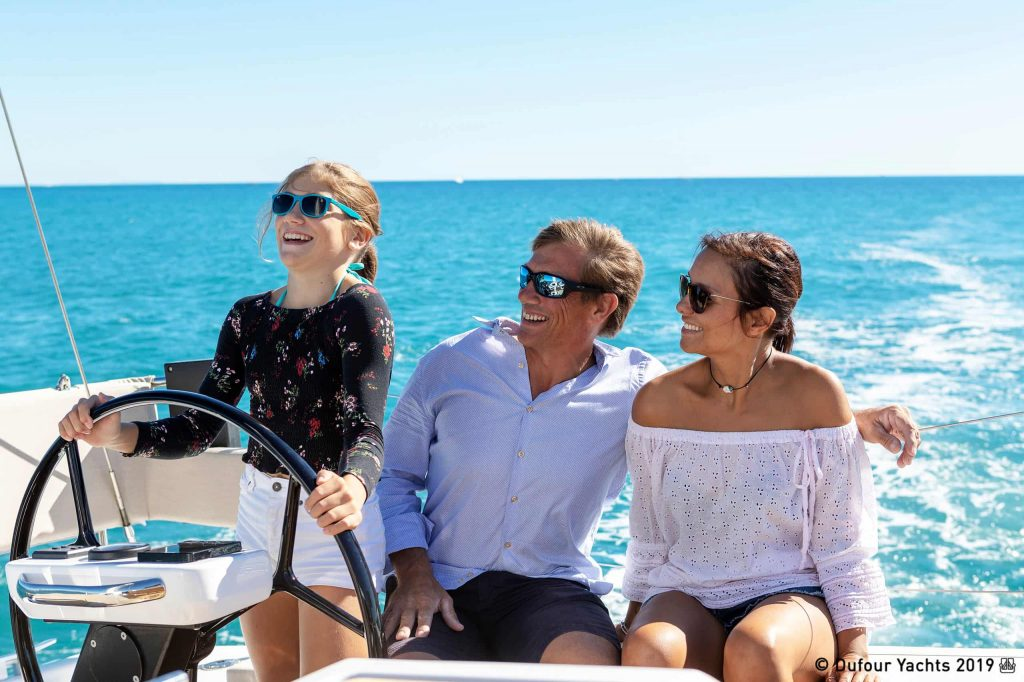 A family standing near the helm of a yacht